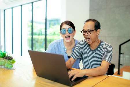 asian man and woman make a exciting face and looking to computer screen Stock fotó