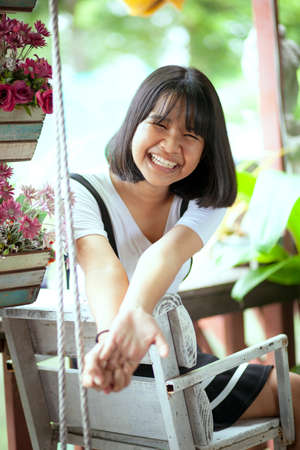 toothy smiling face of asian teenager sitting on wood desk