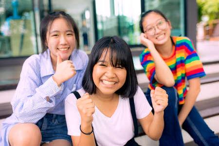 cheerful asian teenager at school bulding
