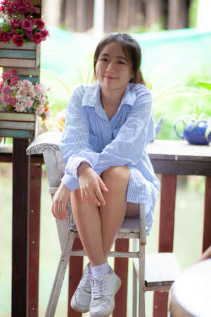 cheerful asian teenager, relaxing on wood desk