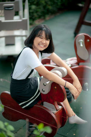 smiling face of asian teenager in public park