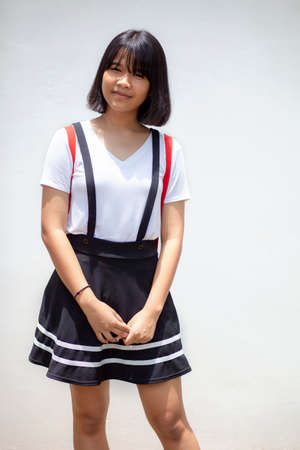portrait pretty asian teenager standing against white wall