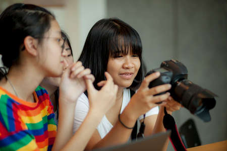 asian teenager looking on back screen of dslr camera in hand