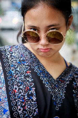asian teenager wearing sunglasses