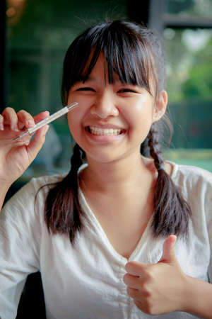 asian teenager toothy smiling and holding body thermometer in hand Stock fotó
