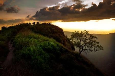 tourist on mountain top against beautiful sunset sky