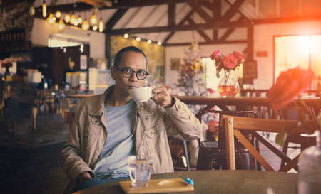 asian man drinking hot coffee in cafe