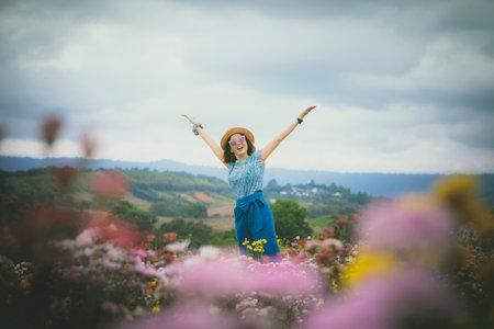 cheerful asian woman in beautiful flower garden