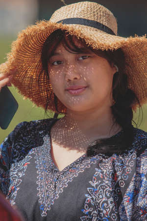 asian teenager wearing straw hat with happiness face