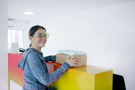 woman holding cardboard box toothy smiling face with happiness