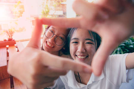 two asian teenager toothy smiling face with happiness mood