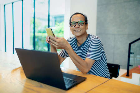 asian freelance man working of laptop computer toothy smiling face