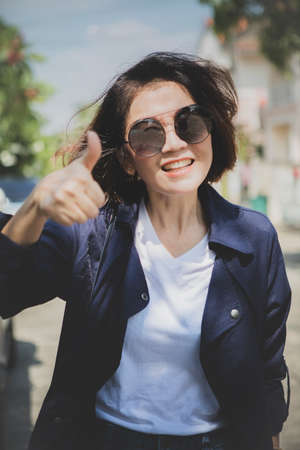 woman toothy smiling face show right thumb outdoor