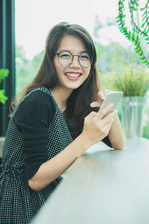 asian younger woman laughing with happiness emotion reading smart phone 版權商用圖片