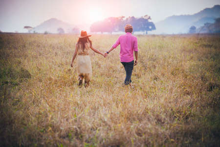 couples holding hand walking in ranch field and sun light background 版權商用圖片