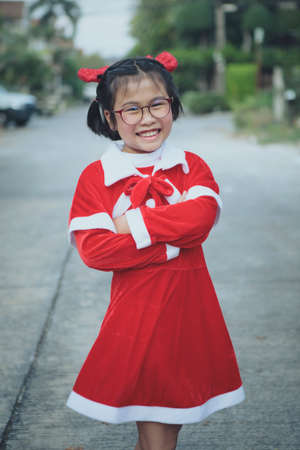 asian girl wearing red suit of santa claus toothy smiling with happiness face