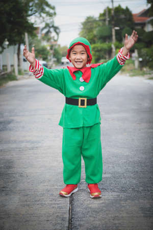 asian children wearing red and green suit of santa claus theme standing outdoor