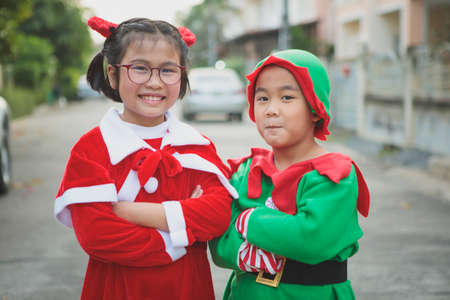 asian girl and boy wearing santa claus suit playing with happiness outdoor 版權商用圖片