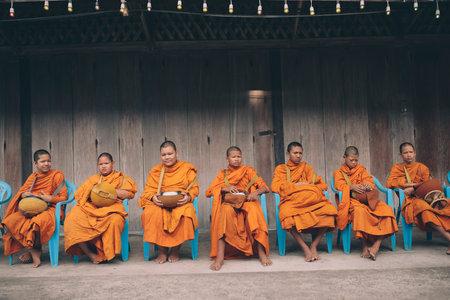 prachuap khiri khan thailand -june2,2019 : thai monk sitting on desk in townstreet waiting for morning food offering