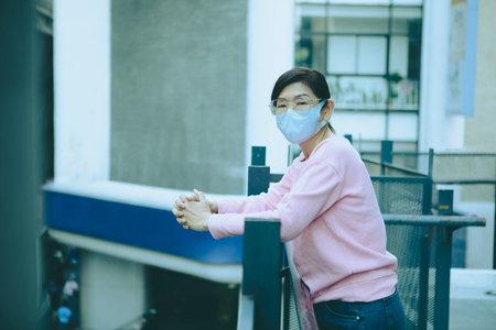 asian woman wearing protection mask standing bulding outside 版權商用圖片
