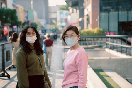 two asian woman wearing protection mask standing on bangkok  city street 版權商用圖片