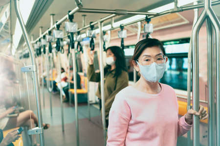 asian woman wearing protection mask standing in underground train Stock fotó