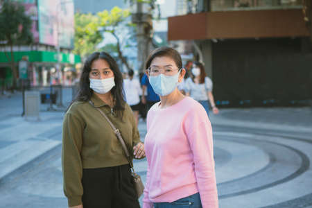 two asian woman wearing protection mask standing at bangkok city street