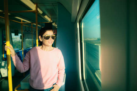 asian woman wearing sunglasses standing in city sky trains
