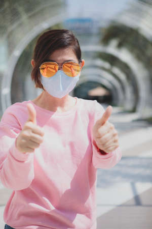 woman wearing protection mask standing outdoor raising hand for good healthy