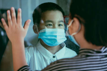 asian children wearing protection mask standing at home door