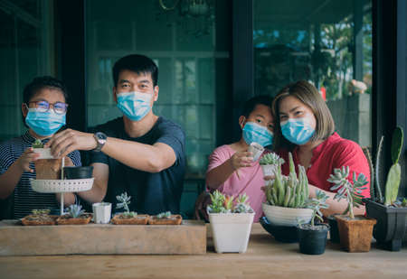 asian family wearing face mask planting cactus at home