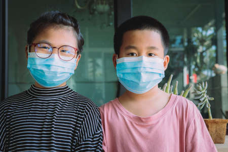 two asian children wearing protection face mask standing at home