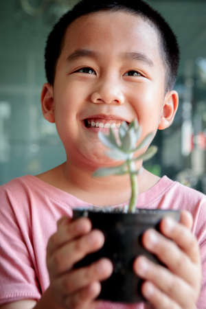 toothy smiling face of asian children holding succulent pot in hand Stock fotó
