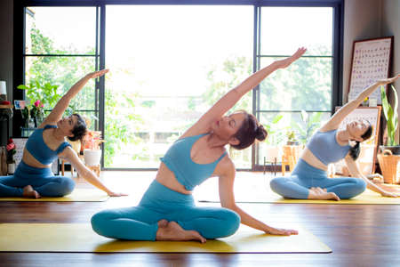 three asian woman doing yoga in home living room