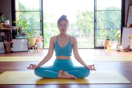 asian woman doing yoga at home living room Stock fotó