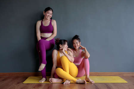 three asian woman wearing yoga suit sitting in fitness room Stock fotó