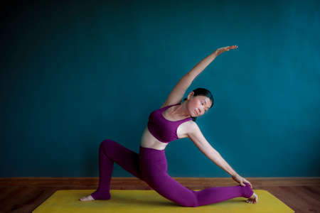 asian woman doing yoga warrior pose and home living room