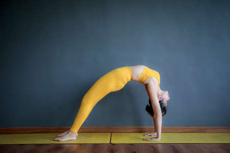 asian woman doing yoga pose in home living room