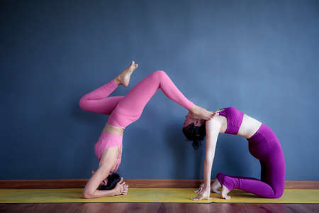 two woman doing yoga pose in home living room Stock fotó