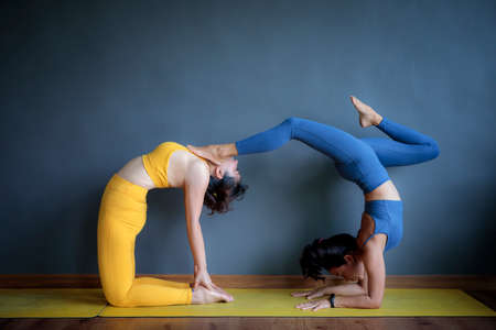 two asian woman doing yoga pose in on floor