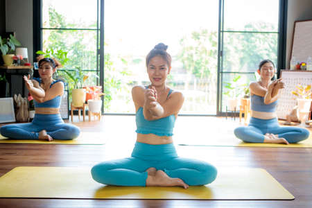 three asian woman doing yoga pose in home living room