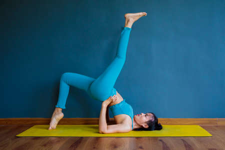 asian woman doing yoga pose at home living room