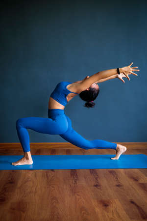 asian woman doing yoga pose on blue mat
