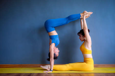 two asian woman doing yoga pose in home living room