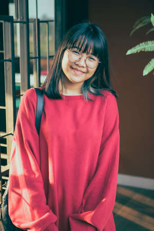 asian teenager wearing red casual with smiling face