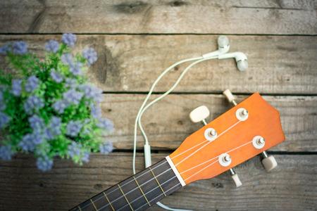 earphone: Ukulele and flower, earphone on wooden background Stock Photo