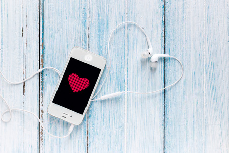 earphone: smartphone with earphone and heart symbol on screen (phone, smartphone, mobile) Stock Photo