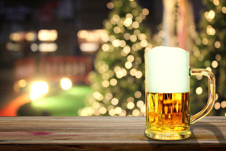 Beer in glass on wooden table,Christmas light background Stock Photo