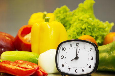 alarm clock with fresh vegetables for cooking