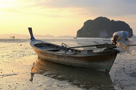 ebb: Fishing boat stranded on mud at low tide, Ao Thalane, Krabi province, Thailand  Stock Photo